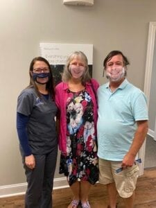 Two happy patients and a team member of AHA with a face mark inside our office